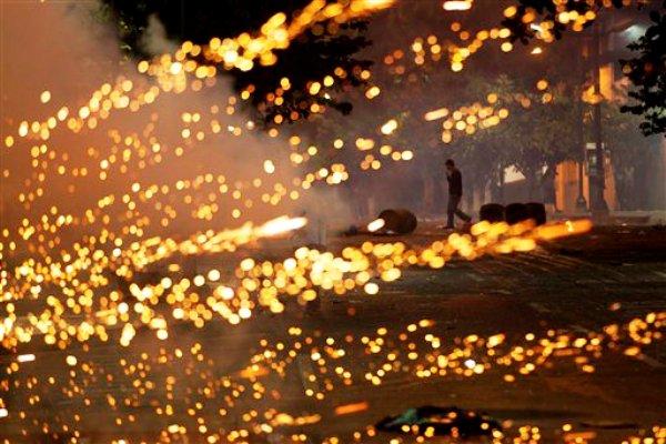 Un manifestante opositor al gobierno camina cerca de fuegos artificiales lanzados contra elementos de la Guardia Nacional Bolivariana el sábado 22 de marzo de 2014 en Caracas, Venezuela. Dos personas más murieron como resultado de los enfrentamientos de este día entre simpatizantes y opositores del presidente Nicolás Maduro. (Foto de AP/Esteban Felix)