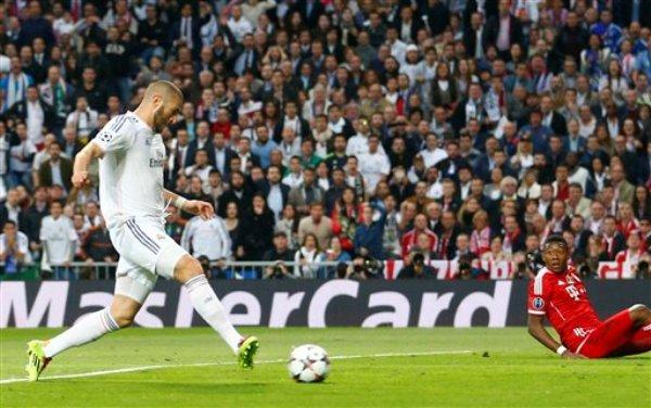 Karim Benzema del Real Madrid anotar un gol ante la mirada de David Alaba del Bayern Munich en las semifinales de la Liga de Campeones el miércoles 23 de abril de 2014. (AP Foto/Paul White)