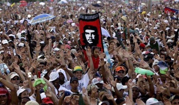 """En esta imagen del 20 de septiembre de 2009 una persona sostiene un cartel con la imagen de Ernesto """"Che"""" Guevara entre la multitud de asistentes al concierto """"Paz sin fronteras? en la Plaza de la Revolución en La Habana, Cuba. El gobierno de Estados Unidos planeó la creación de un ?Twitter cubano?, una red de comunicaciones diseñada para socavar al gobierno comunista de la isla, creada con compañías pantalla y financiada a través de un banco extranjero, ha conocido The Associated Pres. (Foto AP/Javier Galeano, Archivo)"""