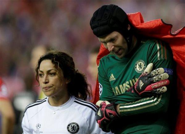 El arquero checo Petr Cech, del Chelsea, se sujeta el brazo, cubierto por una frazada, mientras abandona definitivamente la cancha durante la ida de las semifinales de la Liga de Campeones de Europa, frente al Atlético de Madrid, el martes 22 de abril de 2014 (AP Foto/Paul White)