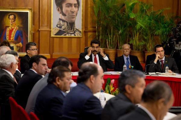 El presidente venezolano Nicolás Maduro (centro al fondo) mira hacia los líderes de la oposición al comienzo de una reunión en el Palacio de Miraflores en Caracas, Venezuela, el jueves 10 de abril de 2014. El papa Francisco ha exhortado a realizar conversaciones dirigidas a la reconciliación entre las partes desde que las protestas comenzaron a principios de febrero. (Foto AP/Fernando Llano)