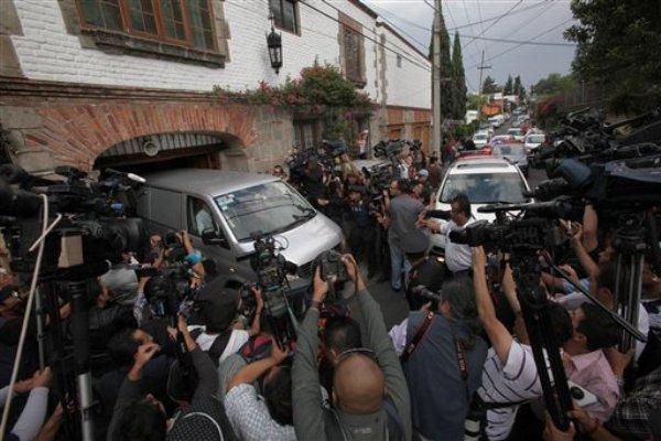 Un vehículo de una empresa funeraria rodeado de fotógrafos y periodistas abandona la casa del laureado escritor Gabriel García Márquez en ciudad de México, el jueves 17 de abril de 2014. (AP Photo/Marco Ugarte)