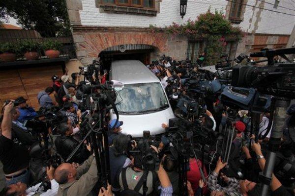 Un vehículo de una empresa funeraria es rodeado por fotógrafos y reporteros cuando llega a la casa del laureado escritor colombiano Gabriel García Márquez en Ciudad de México, el jueves 17 de abril de 2014.  (AP Photo/Marco Ugarte)