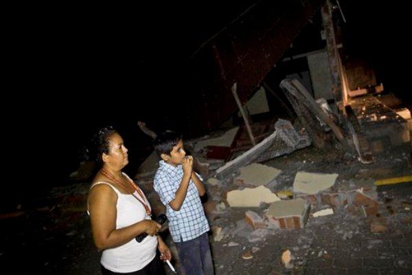 Una mujer y un niño permanecen cerca de una vivienda  por un sismo en la localidad de Nagarote, en el oeste de Nicaragua, el jueves 10 de abril de 2014. El temblor de magnitud 6,1 dañó decenas de viviendas, en las que se vinieron abajo techos, muros y vigas, y dejó al menos 23 heridos en la región, según las autoridades.(AP Foto/Esteban Félix)