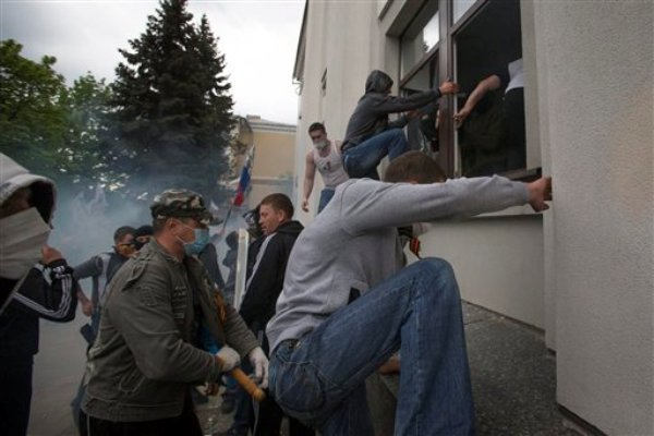 Activistas prorrusos toman por asalto un edificio administrativo en el centro de Lugansk, una de las ciudades más grandes del este de Ucrania, el martes 29 de abril de 2014. (Foto AP/Alexander Zemlianichenko)