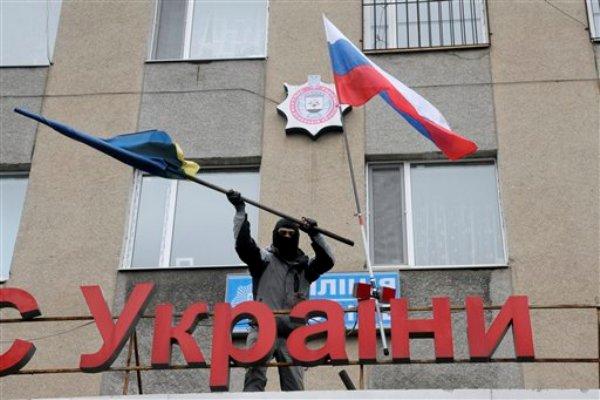 Un enmascarado prorruso se deshace de una bandera de Ucrania después de reemplazarla con una de Rusia en una comisaría que fue asaltada por individuos en Horlivka.