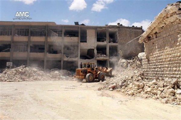 Esta foto proporcionada por el Aleppo Media Center (AMC), que ha sido verificada por la AP, muestra a un buldócer removiendo los escombros de una escuela destruida tras un ataque aéreo del gobierno sirio en Alepo, Siria, el miércoles 30 de abril de 2014. (AP Foto/Aleppo Media Center AMC)