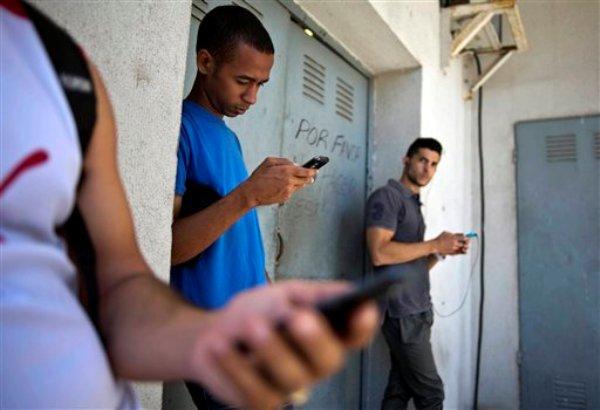 """Estudiantes reunidos detrás de un negocio intentan encontrar una señal de internet para sus teléfonos multifuncionales en La Habana, Cuba, el 1 de abril de 2014. El gobierno de Costa Rica dice que aguarda una explicación de Estados Unidos sobre el programa secreto """"Twitter Cubano"""" que se pretendía emprender desde el interior del país centroamerciano para causar agitación en Cuba. (AP Foto/Ramón Espinosa)"""
