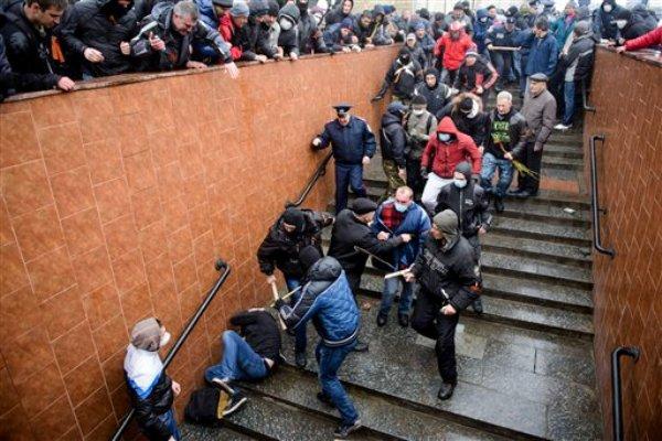 Partidarios del gobierno de Moscú golpean a un activista de inclinación occidental que se cubre la cabeza en una escalera durante una manifestació a favor de Rusia en Jarkiv, Ucrania, el domingo 13 de abril de 2014. (Foto AP/ Olga Ivashchenko)