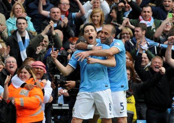 El francés Samir Nasri, del Manchester City, a la izquierda, celebra con el argentino Pablo Zabaleta tras anotar un gol contra el West Ham en la última fecha de la liga Premier, en el estadio Etihad, en Manchester, Inglaterra, el domingo 11 de mayo de 2014. El Man City se coronó el domingo campeón de la Premier. (AP Foto/Rui Vieira)