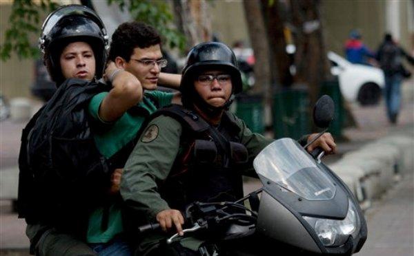 Guardias nacionales bolivarianos motorizados llevan detenido a un manifestante antigubernamental durante una protesta para demandar la libertad de estudiantes detenidos en Caracas, Venezuela, el lunes 12 de mayo de 2014.(AP Photo/Fernando Llano)