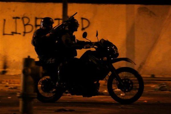 En imagen de archivo del 28 de febrero de 2014 se aprecia a oficiales de la Guardia Nacional Bolivariana avanzar a bordo de una motocicleta para dispersar una manifestación en Caracas, Venezuela. (Foto de AP/Fernando Llano, archivo)