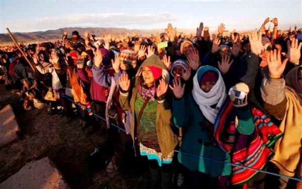 La gente alza las manos a los primeros rayos del sol en los ritos del Año Nuevo Andino en las ruinas de Tiwanaku, Bolivia, sábado 21 de junio de 2014. Los indígena(AP Foto/Juan Karita)