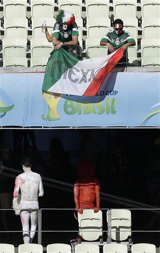 Aficionados mexicanos recogen su bandera tras la derrota ante Holanda, el domingo 29 de junio de 2014, en Fortaleza, Brasil, tras un duelo por los octavos de final de la Copa del Mundo (AP foto/Themba Hadebe)