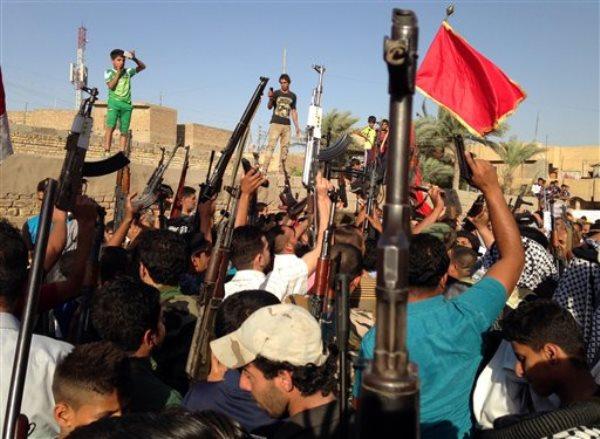 Combatientes chiíes alzan sus armas y gritan consignas contra el grupo Estado Islámico para Irak y el Levante en Bagdad el 15 de junio de 2014. (Foto AP)