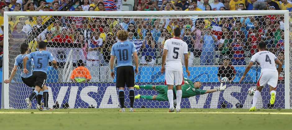 Fortaleza (Brazil), 14/06/2014.- Edinson Cavani (L) of Uruguay scores the 1-0 lead from the penalty spot against Costa Rica's goalkeeper Keilor Navas (back R) during the FIFA World Cup 2014 group D preliminary round match between Uruguay and Costa Rica at the Estadio Castelao in Fortaleza, Brazil, 14 June 2014.