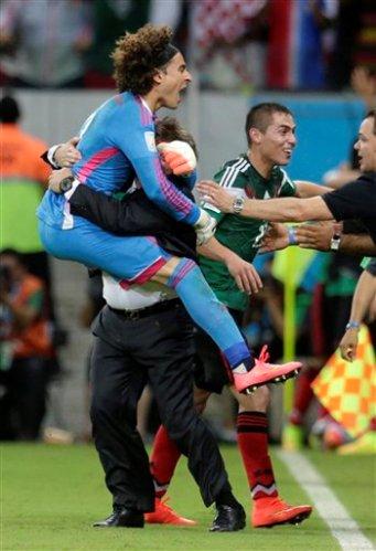 El arquero de México, Guillermo Ochoa, izquierda, abraza al técnico Miguel Herrera tras el segundo gol de México en el triunfo 3-1 sobre Croacia en la Copa del Mundo el lunes, 23 de junio de 2014, en Recife, Brasil. (AP Photo/Petr David Josek)
