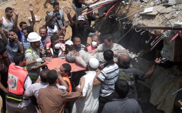 Rescatistas palestinos y civiles extraen un cadáver de entre los escombros de una casa destruida por un ataque isralí en la Ciudad de Gaza el 21 de julio del 2014. (AP Foto/Khalil Hamra)