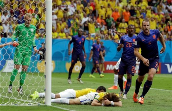 El jugador de Brasil, David Luiz, centro en el suelo, tras una jugada en el área de Holanda en el partido por el tercer lugar el sábado, 12 de julio de 2014, en Brasilia. (AP Photo/Hassan Ammar)