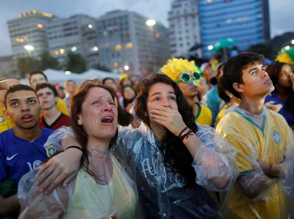 Hinchas de Brasil lloran al ver la derrota de su selección ante Alemania en la semifinal de la Copa del Mundo, mediante una pantalla gigante emplazada en la playa de Copacabana, el martes 8 de julio de 2014 (AP Foto/Leo Correa)