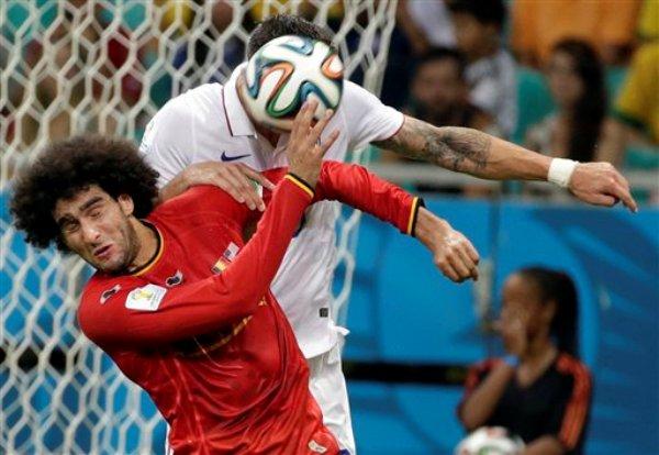 Marouane Fellaini, de Bélgica, salta mientras Geoff Cameron, de Estados Unidos, conecta un balón con la cabeza, durante el partido de la Copa del Mundo disputado el martes 1 de julio de 2014 en Salvador, Brasil (AP Foto/Felipe Dana)
