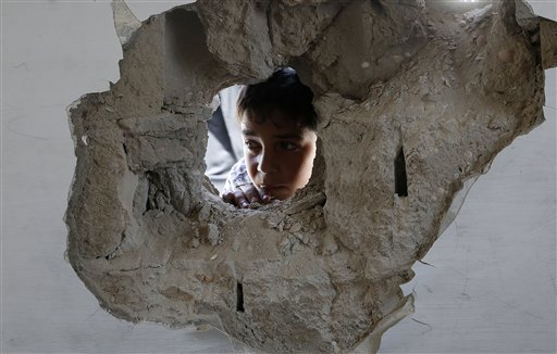 Un niño mira a través de un boquete luego de un ataque usraelí a la escuela de la ONU Abu Hussein en el campo de refugiados Jebaliya en el norte de la Franja de Gaza, miércoles 30 de julio de 2014. Proyectiles disparados por tanques israelíes cayeron el miércoles en una atestada escuela de la ONU que alberga a refugiados de la guerra en Gaza, matando a 15 palestinos e hiriendo a 90 tras destrozar dos aulas, dijeron un funcionario de salud y un portavoz de la agencia de ayuda de la ONU.. (AP Photo/Hatem Moussa)