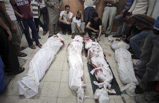 Palestinos lloran junto a los cadáveres de familiares muertos en un ataque de Israel contra una escuela de la ONU en el campo de refugiados de Jebaliya, en Beit Lahiya, en el norte de la Franja de Gaza, el miércoles, 30 de julio del 2014. (Foto AP/Khalil Hamra)