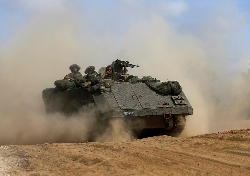 Un blindado israelí circula en la frontera entre Israel y Gaza el domingo 13 de julio de 2014. Israel desplegó tropas brevemente dentro de la franja de Gaza el domingo por primera vez. (Foto de AP/Tsafrir Abayov)