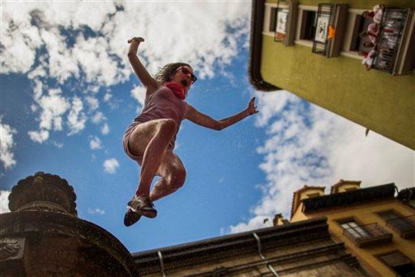 """Una juerguista salta desde una fuente hacia la multitud después del lanzamiento del cohete """"El Chupinazo"""", que marca la inauguración oficial de las fiestas de San Fermín 2014 en Pamplona, España, el domingo 6 de julio de 2014. (Foto AP/Andres Kudacki)"""