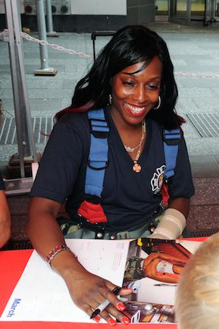 La bombera Danae Mines firma una copia del calendario Héroes 2015. (Foto AP/FDNY)