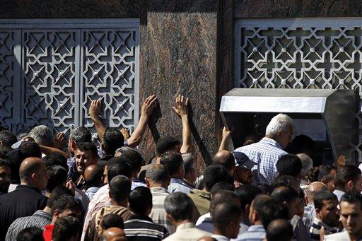 Palestinos reunidos para sacar dinero de cajeros automáticos en Ciudad de Gaza, el 17 de julio de 2014.  Israel y Hamas comenzaron un alto el fuego humanitario de cinco horas, en el décimo día de combates. El Banco de Palestina abrió una de sus oficinas en el barrio de RImal, en Gaza, atrayendo a cientos de personas que intentaban retirar dinero.  (AP Photo/Lefteris Pitarakis