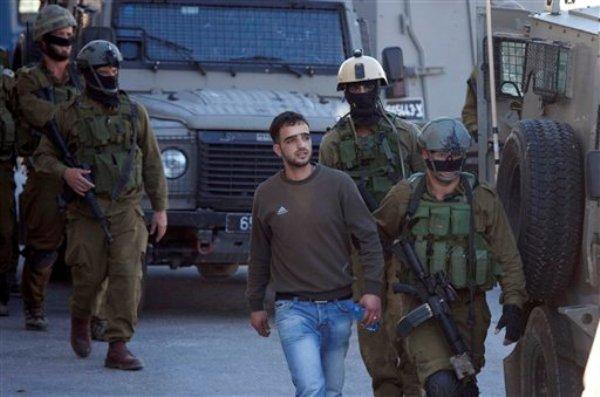 Soldados israelíes arrestan a un palestino en la ciudad de Hebrón, en Cisjordania, el sábado 11 de junio de 2014. Las fuerzas de seguridad israelíes peinan Cisjordania en un intento por encontrar a tres adolescentes israelíes que desaparecieron el jueves en la noche en la región, que a decir de la autoridad palestina, esta bajo absoluto control israelí. (AP Foto/Majdi Mohammed)