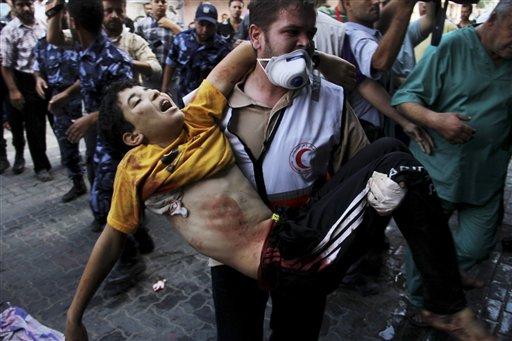 Un médico palestino carga a un niño herido y lo lleva a un hospital en Khan Younis, en el sur de la Franja de Gaza, el miércoles 23 de junio de 2014. (Foto AP/Hatem Ali)