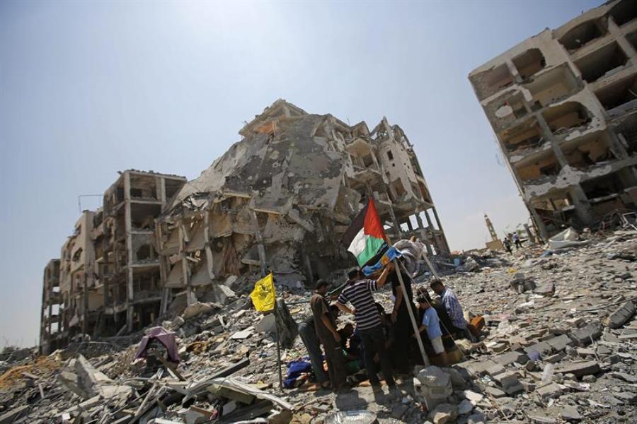 Un grupo de palestinos se reúne entre los escombros de las torres Al-Nada en la ciudad de Beit Lahia (Franja de Gaza) hoy, lunes 11 de agosto de 2014.