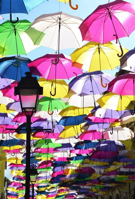 Fotografía facilitada por la empresa Sextafeira, de una calle de la pequeña localidad de Águeda, invadida de color en forma de paraguas flotantes.