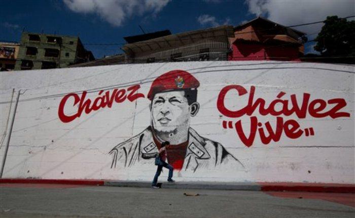 Un gran mural del extinto presidente venezolano Hugo Chávez en el barrio 23 de Enero de Caracas, 17 de julio de 2014. En 2010, Chávez hizo aprobar por el Congreso venezolano la prohibición de que grupos locales reciban fondos de Estados Unidos. Sin embargo, el Senado en Washington estudia un proyecto para elevar los fondos que envía el Departamento de Estado a grupos prodemocráticos en el país sudamericano. (AP Foto/Fernando Llano)