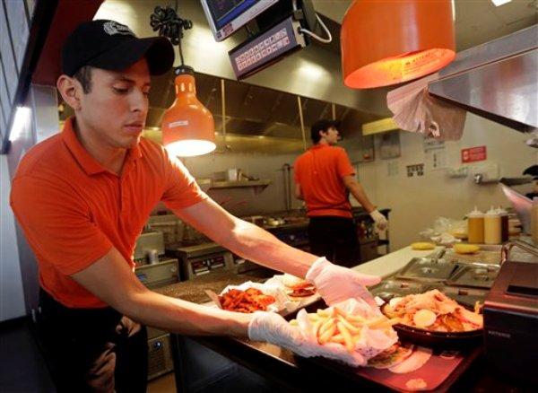 En esta fotografía tomada el viernes 15 de agosto de 2014 Ismael Telleria prepara un pedido en el restaurante de la cadena colombiana El Corral en Miami. (AP foto/Alan Diaz)