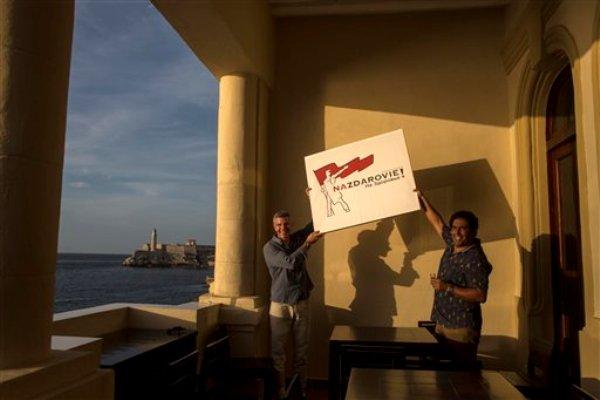 Fotografía del 20 de agosto de 2014 en la que aparecen Gregory Biniowsky (izquierda) y su socio de negocios Yociel Marrero posando con el letrero de su nuevo restaurante Nazdarovie, en la terraza del negocio, con vista al océano, en La Habana, Cuba.  (Foto AP/Ramón Espinosa)