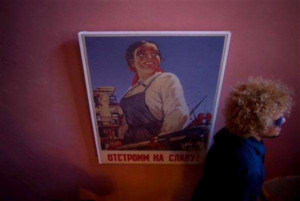 Fotografía del 20 de agosto de 2014 de un comensal que pasa junto a la reproducción de un cartel de propaganda soviética en la entrada del nuevo restaurante Nazdarovie, durante un ensayo previo a la inauguración en La Habana, Cuba.  (Foto AP/Ramón Espinosa)
