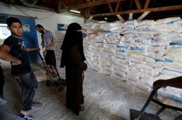 Palestinos apilan bolsas de harina en un centro de distribución de alimentos de la ONU en el campo de refugiados Shati en Gaza, miércoles 6 de agosto de 2014. Israel y Hamas iniciaron conversaciones indirectas el miércoles sobre un nuevo acuerdo fronterizo para la Franja de Gaza, en el segundo día de un cese de fuego que puso fin a un mes de guerra. (AP Foto/Hatem Moussa)