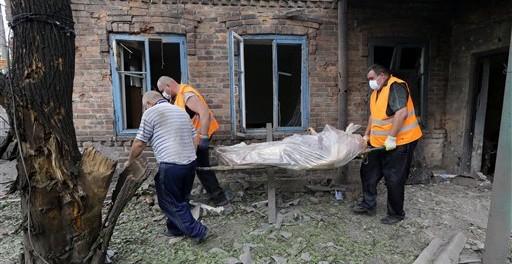Rescatistas cargan el cuerpo de una mujer que murió durante un bombardeo en Donetsk, en el oriente de Ucrania el martes 5 de agosto de 2014. La ONU señaló que que la situación humanitaria en el oriente de Ucrania empeora. (Foto de AP/Sergei Grits)