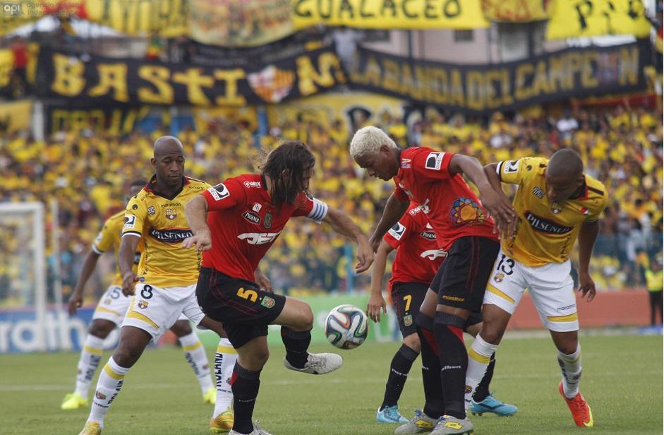 Michael Jackson Quiñonez de Barcelona, Frezzotti y Bone de Deportivo Cuenca pelean un balón ante un estadio Alejandro Serrano Aguilar repleto.