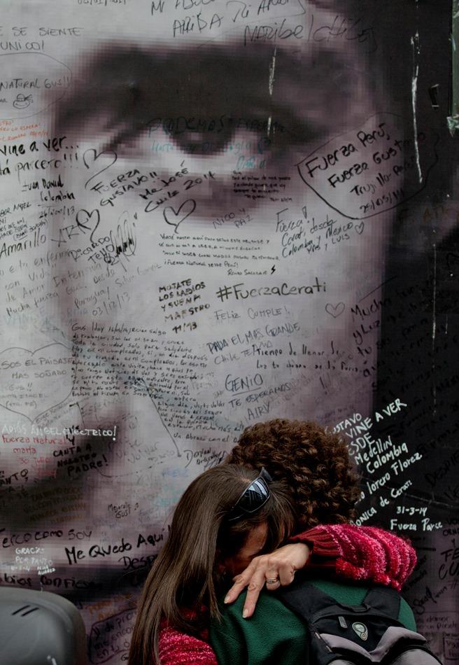 Admiradores del rockero argentino Gustavo Cerati se abrazan frente a un afiche con su imagen frente a la clínica donde estuvo hospitalizado en Buenos Aires, Argentina, el jueves 4 de septiembre de 2014. Cerati murió el jueves 4 de septiembre de 2014, informó su familia.(Foto AP/Natacha Pisarenko)