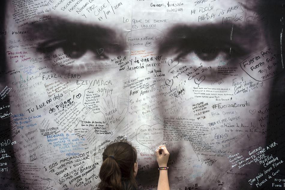 Una fanática del músico argentino Gustavo Cerati escribe un mensaje en un cartel con su imagen hoy, jueves 4 de septiembre de 2014, afuera de la Clínica ALCLA de Buenos Aires (Argentina). EFE/Juan Ignacio Roncoroni