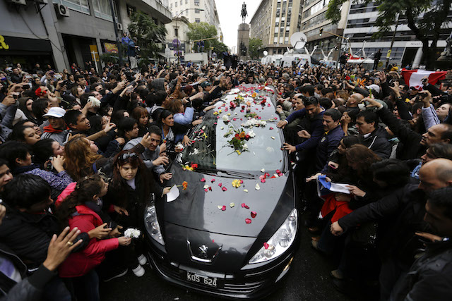 La gente toca la carroza fúnebre con los restos del rockero argentino Gustavo Cerati. (Foto AP/Victor R. Caivano)