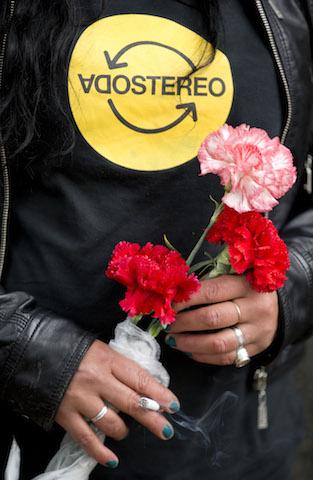 Una mujer sostiene flores al esperar en el cementerio la llegada de la carroza fúnebre del rockero argentino Gustavo Cerati. (Foto AP/Natacha Pisarenko)