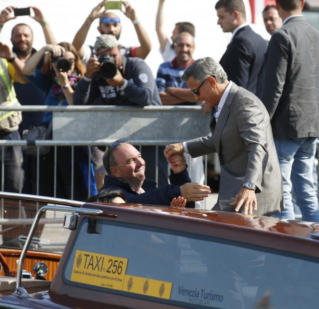 George Clooney, derecha, es ayudado por su taxista acuático Sandro al llegar a Venecia, Italia, el viernes 26 de septiembre de 2014. George Clooney y su prometida Amal Alamuddin llegaron a Venecia el viernes para casarse acompañados por sus seres queridos y fotógrafos que registraban su paso por la romántica ciudad. (Foto AP/Luca Bruno)