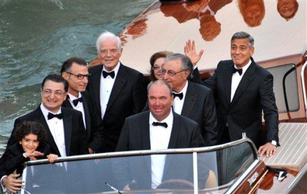 George Clooney saluda desde una lancha taxi antes de casarse con Amal Alamuddin en Venecia, Italia, el sábado 27 de septiembre de 2014. (AP Foto/Luigi Costantini)