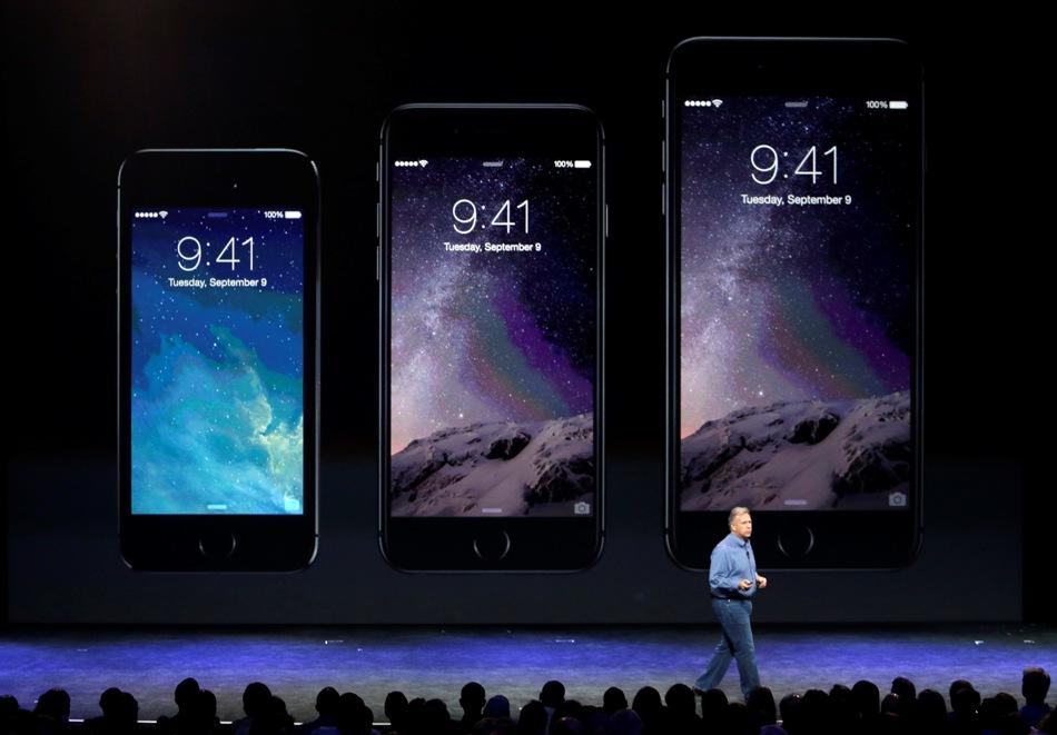 Phil Schiller, vicepresidente sénior de mercadotecnia mundial de Apple, presenta los nuevos teléfonos iPhone 6 (centro) y iPhone 6 plus (derecha), el martes 9 de septiembre de 2014, en Cupertino, California, (Foto AP/Marcio José Sánchez)