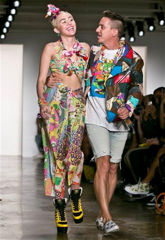 La cantante y actriz Miley Cyrus acompaña al diseñador Jeremy Scott en su recorrido por la pasarela tras el desfile de la colección primavera 2015 de Scott durante la Semana de la Moda el miércoles 10 de septiembre de 2014 en Nueva York.  (Foto AP/Bebeto Matthews)